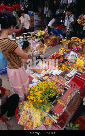 CAMBODIA Siem Reap Display of various religious goods for sale in the old market during Chinese New Year with customers - Stock Photo