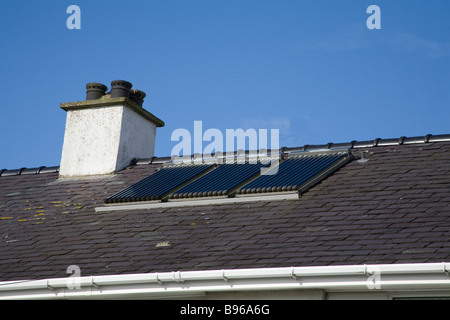 North Wales March A set of three evacuation tube solar panels on the roof of a house to provide cheap renewable - Stock Photo