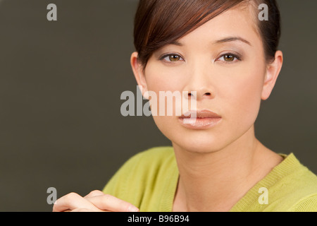 Studio shot of beautiful young oriental woman with a wonderful enigmatic smile - Stock Photo