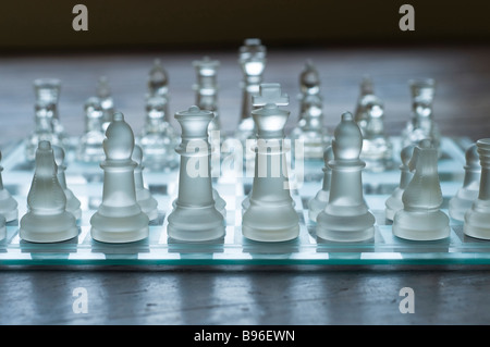 Eye level view of glass chess set on a wooden floor - Stock Photo