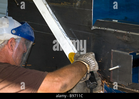 Wearing a safety shield while cutting a piece of plate steel - Stock Photo