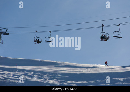 A lone skier sends up a trail of sunlit powder snow underneath a chairlift with more skiers going up against a blue - Stock Photo