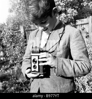 Looking down his viewfinder, a young boy in garden uses a Kodak Brownie reflex box film camera to take a photo, - Stock Photo