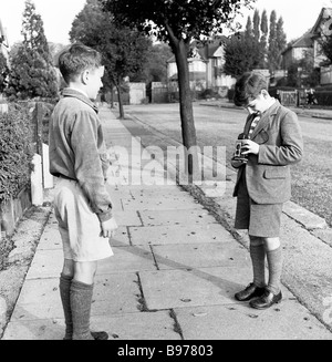 1950s, historical, young boy in school uniform taking a photograph of his school friend with a Kodak Brownie Reflex' - Stock Photo