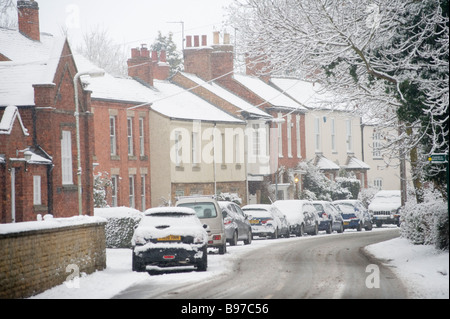 Cars parked outside houses on a snow covered road in a village in england in winter - Stock Photo
