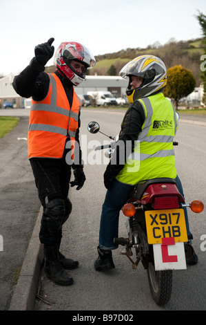 Motorcycle driving instructor and a  pupil wearing high visibility jackets learning to drive a motorbike, UK - Stock Photo