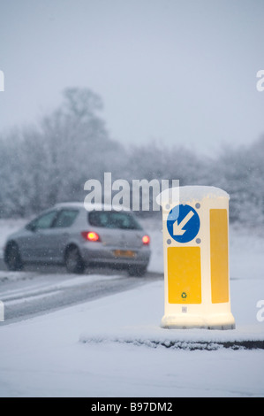 Lone car driving along a snow covered road passing an illuminated traffic bollard on a winters day in england - Stock Photo