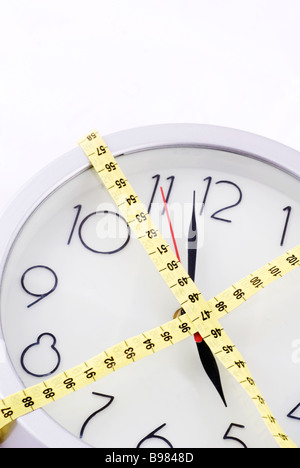 Wall clock wrapped with a tape measure - Stock Photo