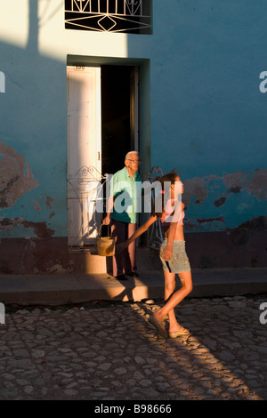 a girl passing an old man in the street in Trinidad, Cuba - Stock Photo