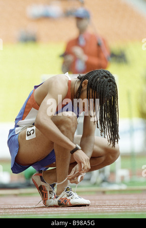 Lacing up sneakers on the racetrack during the 1998 World Juvenile Games - Stock Photo