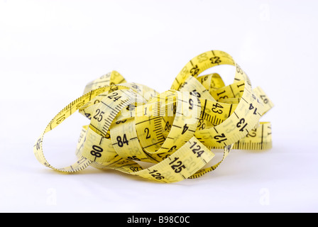 Tangled tape measure isolated against a white background - Stock Photo