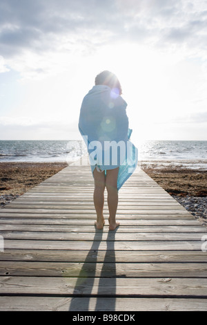 Young child 4-6 standing on jetty looking out towards the sea - Stock Photo