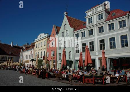 People sitting outside Restaurants and cafes on Town Hall Square Raekoja Plats Historic buildings TALLINN ESTONIA - Stock Photo