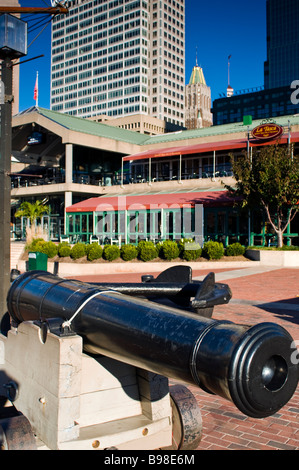 A view of Baltimore Maryland seen from the Inner Harbor with a cannon in the foreground - Stock Photo
