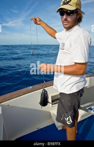 Big game fishing fisherman preparing bonito lure on fishingboat Saint Gilles La Réunion France - Stock Photo