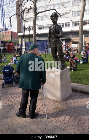 man looking at a charlie chaplin statue in Leicester Square  london - Stock Photo