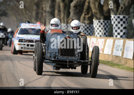 Classic cars of motor racing make their way to the start line at Goodwood Festival of Speed in West Sussex. - Stock Photo