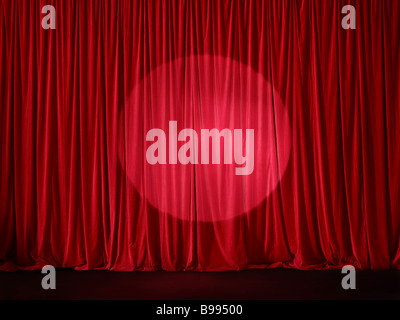 Red stage curtain spotlit - Stock Photo