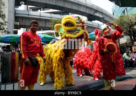 Lion dancers at Erawan Shrine in central Bangkok, Thailand - Stock Photo
