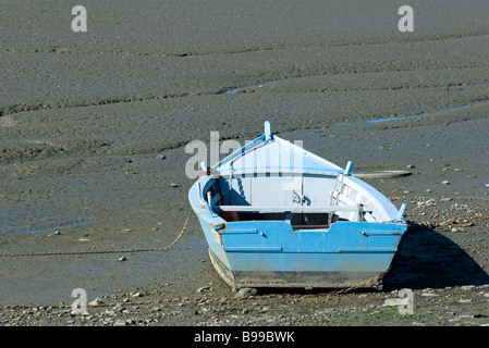 Rowboat stranded on mud flat - Stock Photo