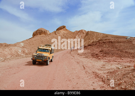 Eilat Mountains, Israel. A jeep with tourists on sightseeing trip drives through the red hills of the Timna National - Stock Photo