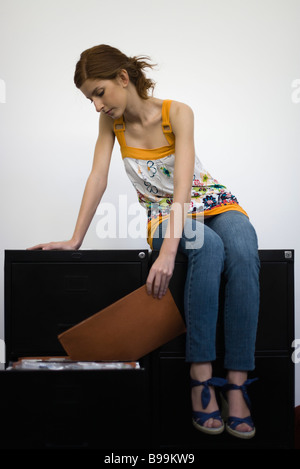 Woman sitting on top of filing cabinets, reviewing contents of file - Stock Photo