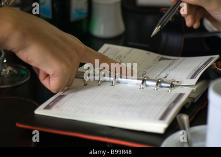 Two people making plans using agenda, one holding pen while the other points to page - Stock Photo