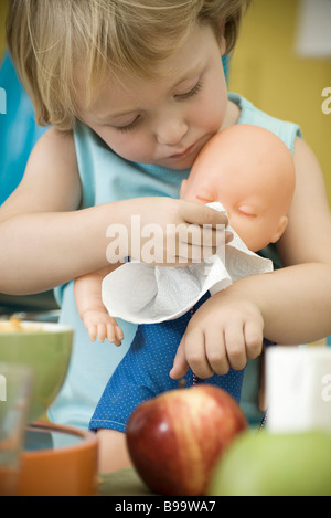 Little girl wiping baby doll's face with paper towel - Stock Photo