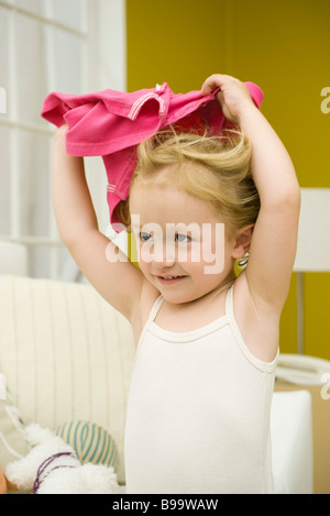 Little girl holding shirt over her head - Stock Photo