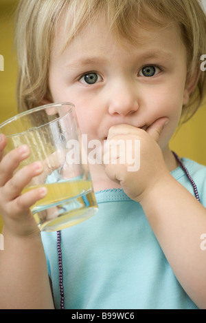 Toddler girl holding glass of juice, covering mouth with one hand - Stock Photo