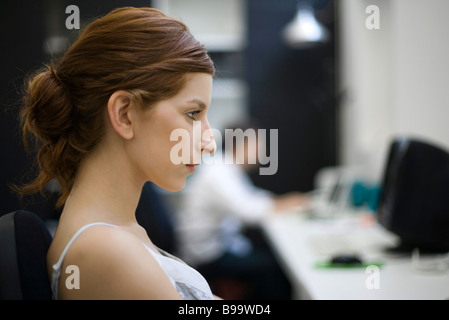 Woman working at desk, profile - Stock Photo