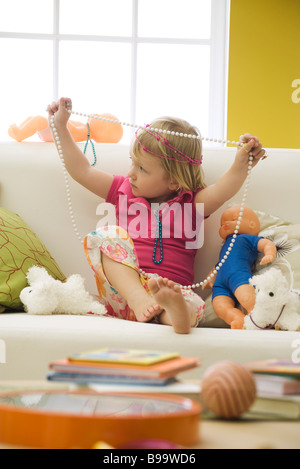 Little girl sitting on sofa with toys, playing with costume jewelry - Stock Photo