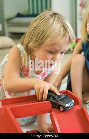 Little girl playing with toy car - Stock Photo