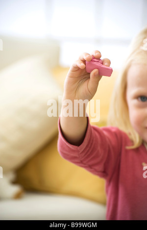 Little girl holding up handful of pink clay, cropped - Stock Photo