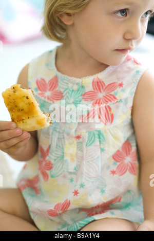Little girl eating bread, looking away - Stock Photo