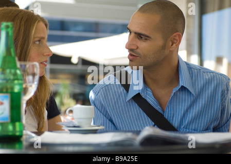 Man and woman sitting in outdoor cafe, having serious conversation - Stock Photo