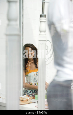 Young woman looking at shoes in shop window - Stock Photo