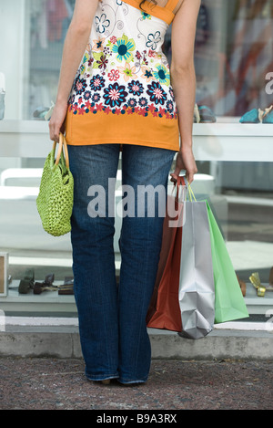 Young woman window shopping, carrying several shopping bags, cropped rear view - Stock Photo