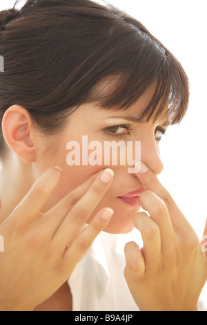 Portrait of a Young Woman Squeezing a Pimple in Her Face - Stock Photo