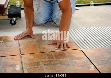 Male Hispanic Lays Ceramic Tile On Cement Floor In Patio Lanai Stock