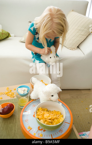 Little girl feeding cereal to stuffed toy - Stock Photo