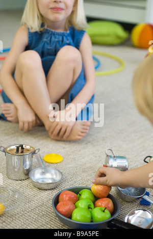 Children sitting on floor, playing with pots and pans, cropped - Stock Photo