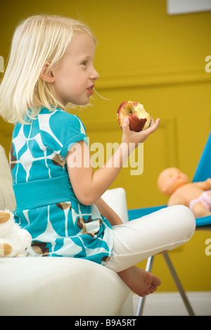 Little girl eating apple on sofa, side view - Stock Photo