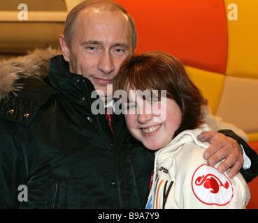 Russian President Vladimir Putin greets figure skater Irina Slutskaya while visiting the Red Square skating rink - Stock Photo