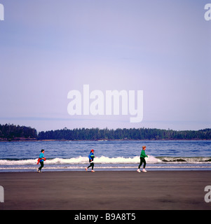 Three Women jogging on Chesterman Beach near Pacific Rim National Park, West Coast, Vancouver Island, BC British - Stock Photo