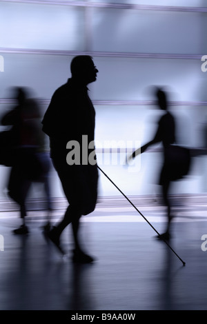 Silhouette of a blind man surrounded by people in haste - Stock Photo