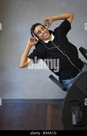 Young man leaning back in chair, listening to headphones - Stock Photo