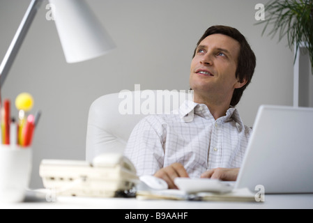 Man sitting at desk, looking up - Stock Photo