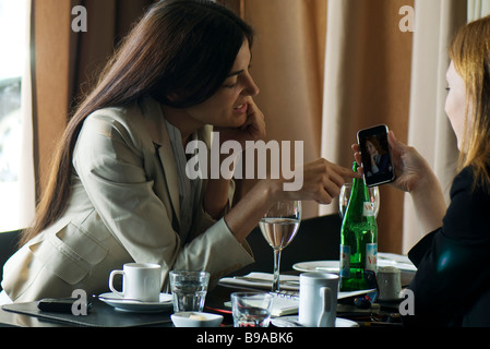Two women sitting in cafe, looking at photophone together - Stock Photo
