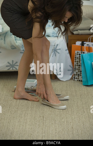 Young woman bending over to put on casual shoes - Stock Photo